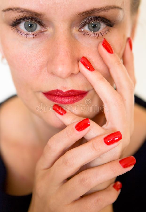 Eine schöne junge Frau berührt ihr Gesicht mit ihren Fingern stockbild