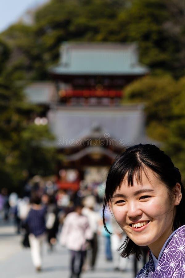 Eine schöne junge Frau, die in die Kamera trägt einen Kimono lächelt stockbilder