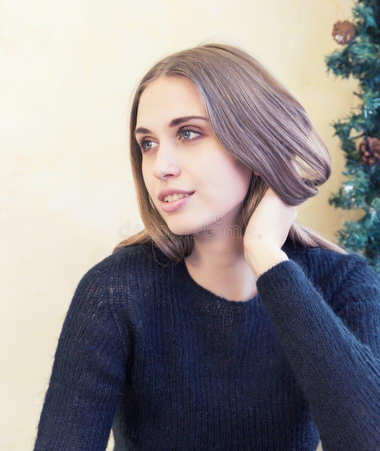 Eine schöne junge Frau im Pullover auf Hintergrund von Weihnachtslichtern lizenzfreie stockfotos