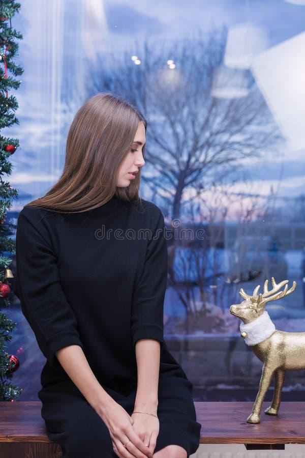 Eine schöne junge Frau im Pullover auf Hintergrund von Weihnachtslichtern lizenzfreies stockfoto