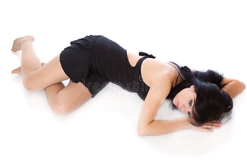Eine schöne junge Frau legt auf den Fußboden lizenzfreie stockfotografie