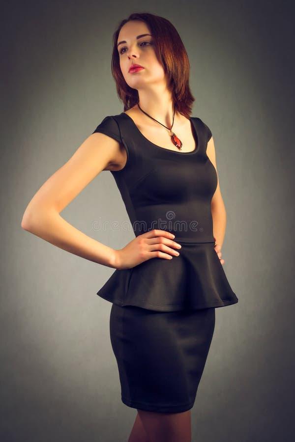 Eine schöne junge Frau mit dem losen Haar in einem schwarzen Kleid lizenzfreie stockfotos