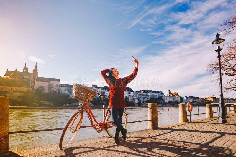 Eine schöne junge Frau mit einem Retro- roten Fahrrad macht ein Foto von in der alten Stadt von Europa auf dem Fluss-Rhein-embank lizenzfreie stockfotos