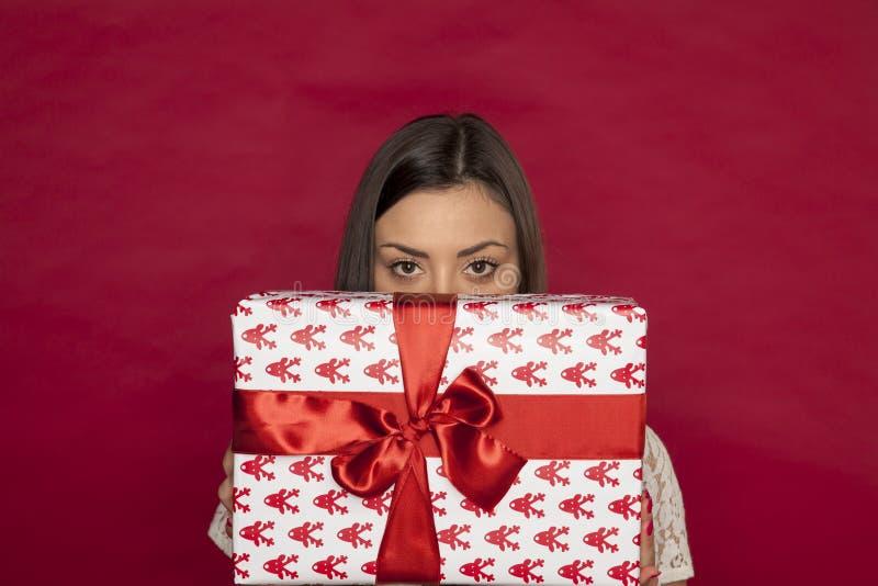 Eine schöne junge Frau versteckt sich hinter einem Geschenk lizenzfreies stockfoto