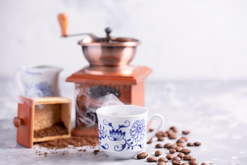 Eine schöne Kaffeezusammensetzung mit einem Platz unter Ihrem Text Körner des Kaffees fallen aus einer Weinlesekaffeemühle heraus lizenzfreies stockfoto