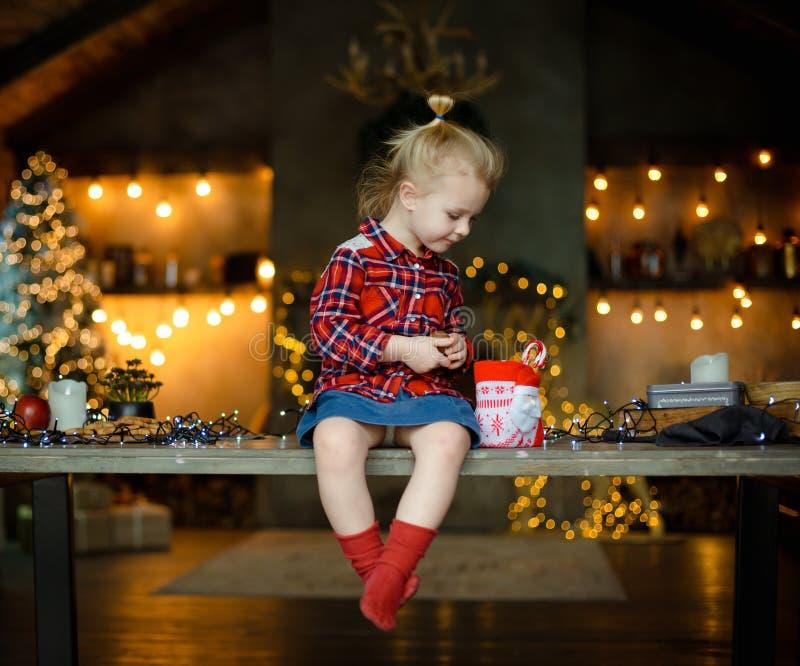Eine schöne kleine Blondine in einem traditionellen karierten Hemd öffnet einen Schokoriegel von ihrem süßen Weihnachtsgeschenk stockbilder