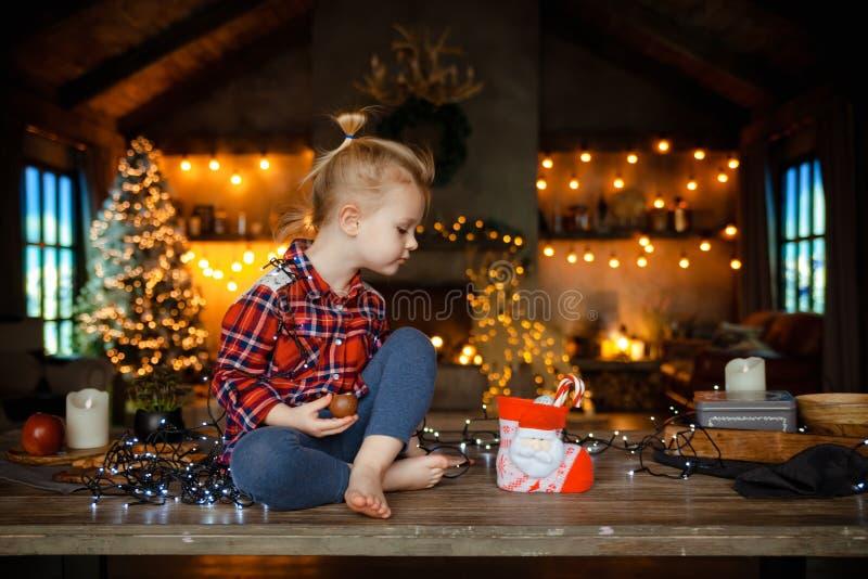 Eine schöne kleine Blondine in einem traditionellen karierten Hemd öffnet einen Schokoriegel von ihrem süßen Weihnachtsgeschenk lizenzfreies stockfoto