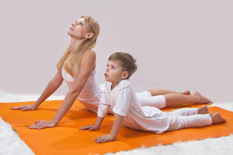 Eine schöne Mutter übt Yoga mit ihrem Sohn lizenzfreie stockbilder