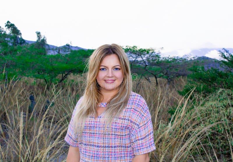 Eine schöne pralle Frau in einem kurzen Kleid Blond Mit einem schönen Lächeln Draußen auf dem Grasland und den Bergen im backgro lizenzfreie stockfotos