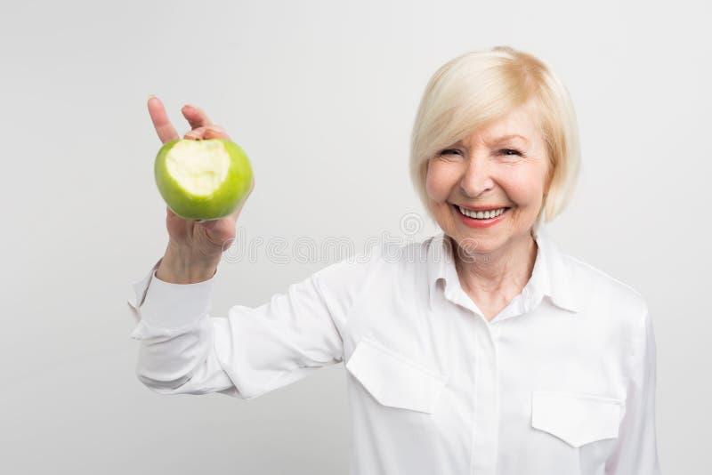Eine schöne reife Frau, die einen gebissenen grünen Apfel in der rechten Hand hält Sie möchte zeigen, dass sie ein gutes und ein  stockfoto