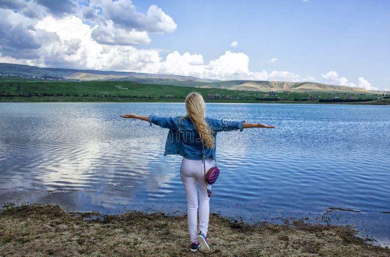 Eine schöne schlanke junge Frau steht mit ihrer Rückseite auf dem Ufer nahe dem Wasser und bewundert die schöne Landschaft lizenzfreies stockbild