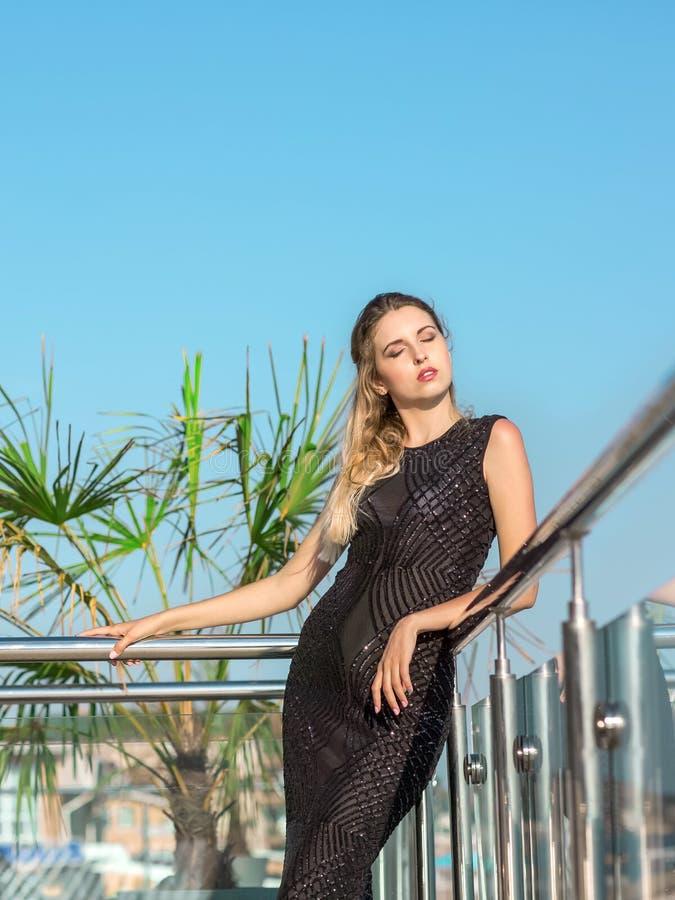 Eine schöne und bezaubernde Frau in einem eleganten Kleid an einer Terrasse des Luxushotels Das hübsche Modell auf einem Hintergr lizenzfreie stockfotografie