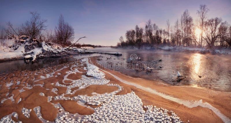 Eine schöne Winter-Morgen-Landschaft: The Sun, das über Forest And The Sandy Shallows des Flusses, bedeckt mit Frost Cryst steigt stockfotos