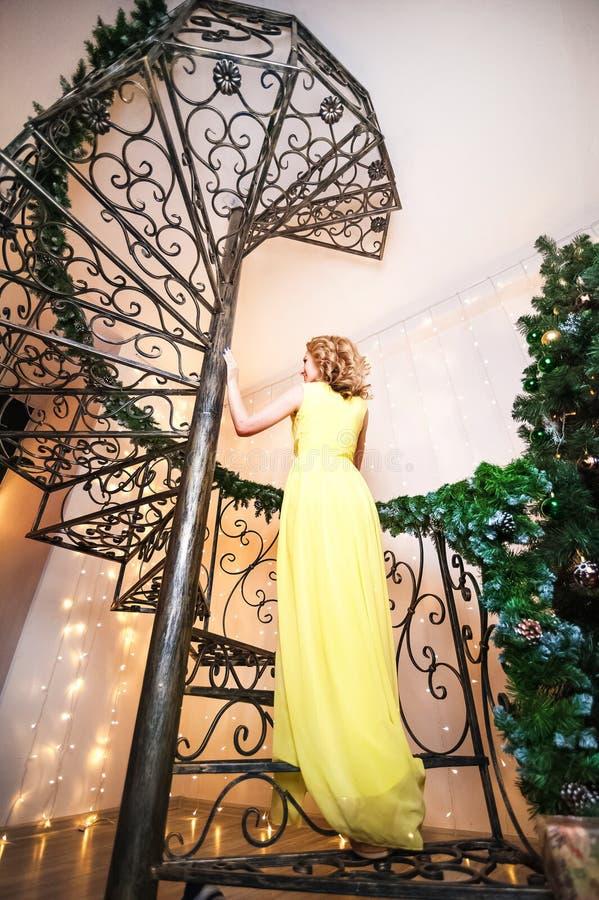 Eine Schönheit in einem gelben langen Kleid steht auf einer Wendeltreppe zurück Ein Mädchen träumt in einem verzierten Wohnzimmer lizenzfreie stockbilder