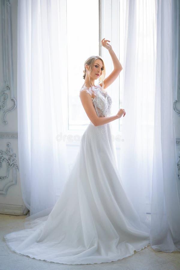 Eine Schönheit in einem weißen Heiratskleid mit einem schönen Make-up und Frisurstände auf dem Hintergrund des Fensters lizenzfreies stockfoto