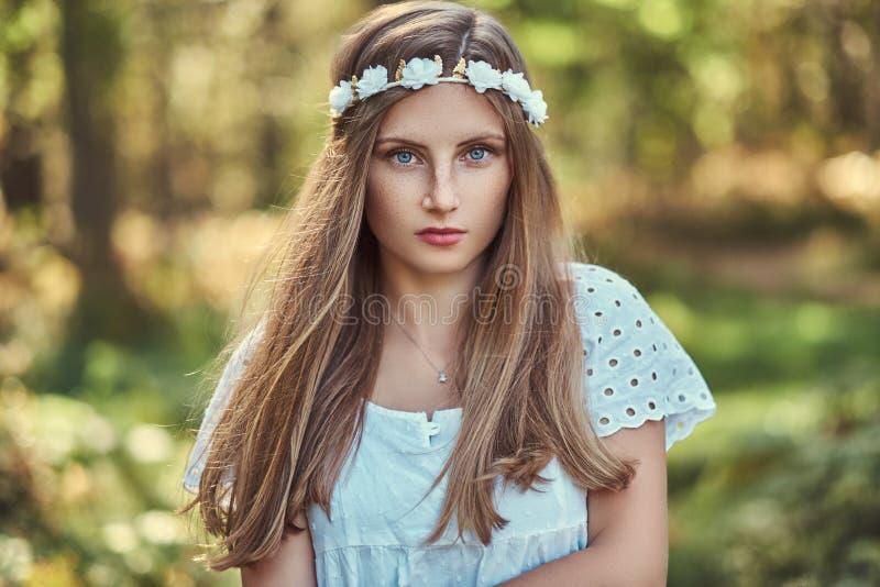 Eine Schönheit in einem weißen Kleid und Weiß windt auf dem Kopf, der in einem grünen Herbstwald aufwirft stockfotografie