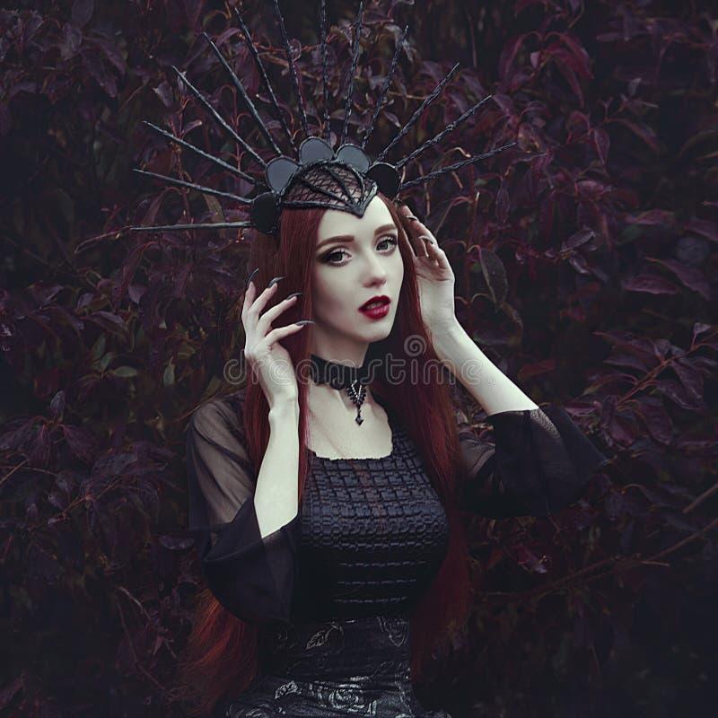 Eine Schönheit mit blasser Haut und dem langen roten Haar in einem schwarzen Kleid und im schwarzen crownk Mädchenhexe mit Vampir lizenzfreie stockfotos