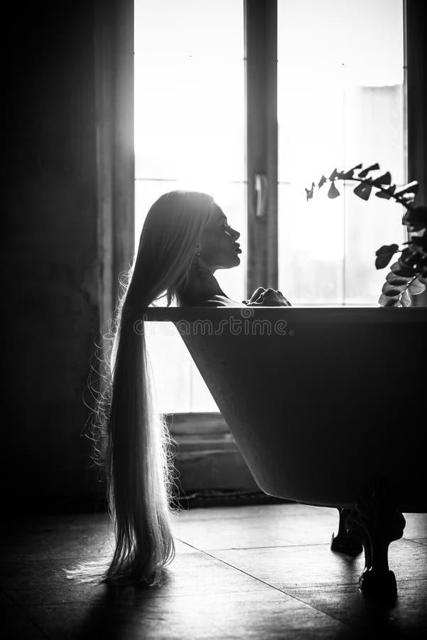 Eine Schönheit mit dem herrlichen langen blonden Haar entspannt sich im Bad Schattenbild einer Frau im Profil, das im Badezimmer  lizenzfreies stockbild