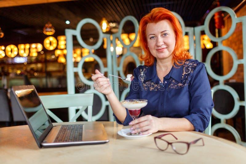 Eine Schönheit mit dem roten Haar, isst einen Nachtisch Zuhause im Café lizenzfreie stockfotografie