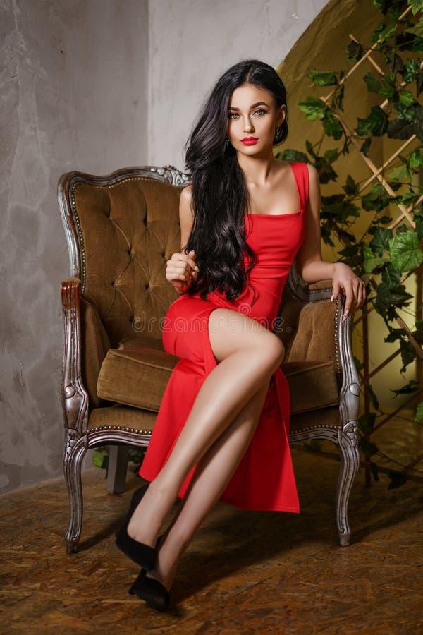 Eine Schönheit mit einem roten Kleid sitzt auf einem Stuhl, einem schönen Make-up und hellen roten Lippen lizenzfreie stockfotos