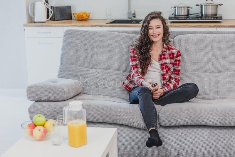 Eine Schönheit sieht fern und sitzt auf der Couch und hält die Fernbedienung in seiner Hand Ein Brunette in a lizenzfreie stockfotos