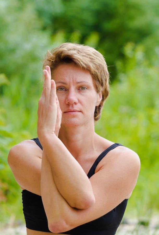 Eine Schönheitsfrau in den sportwears machen verschiedene Yogahaltungen Stärke, pilates draußen Tätigkeit stockfotografie