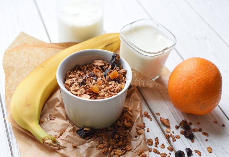 Eine Schüssel des selbst gemachten Granolas, des Glases Joghurts, der frischen Früchte und der Flasche Milch lizenzfreies stockbild