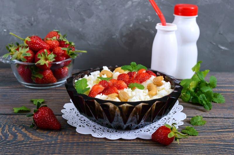 Eine Schüssel frischer selbst gemachter Hüttenkäse mit Erdbeeren, Minze und Nüssen auf einem hölzernen Hintergrund stockbild