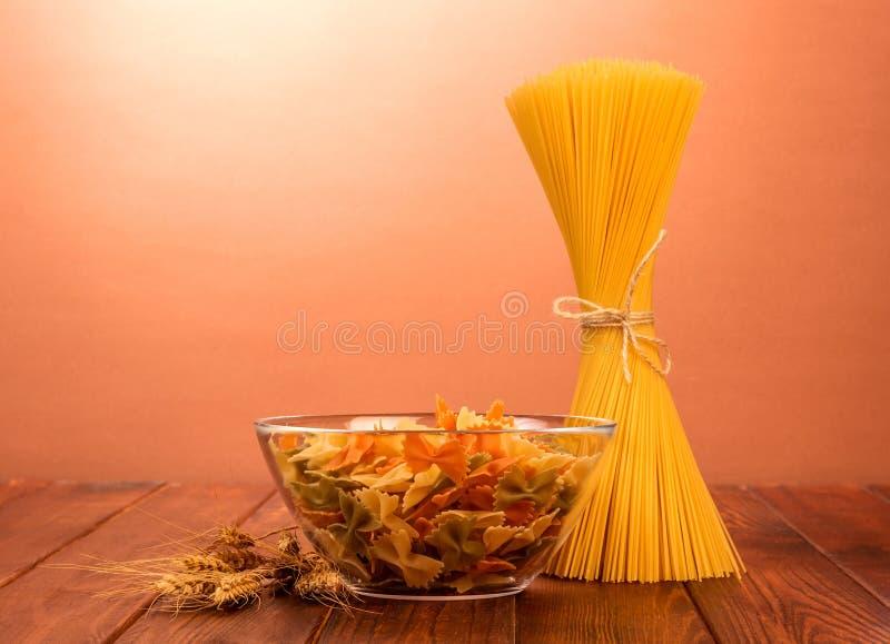 Eine Schüssel Makkaroni farfalle und gebundene Spaghettis stehen auf Re aufgerichtet stockfotografie