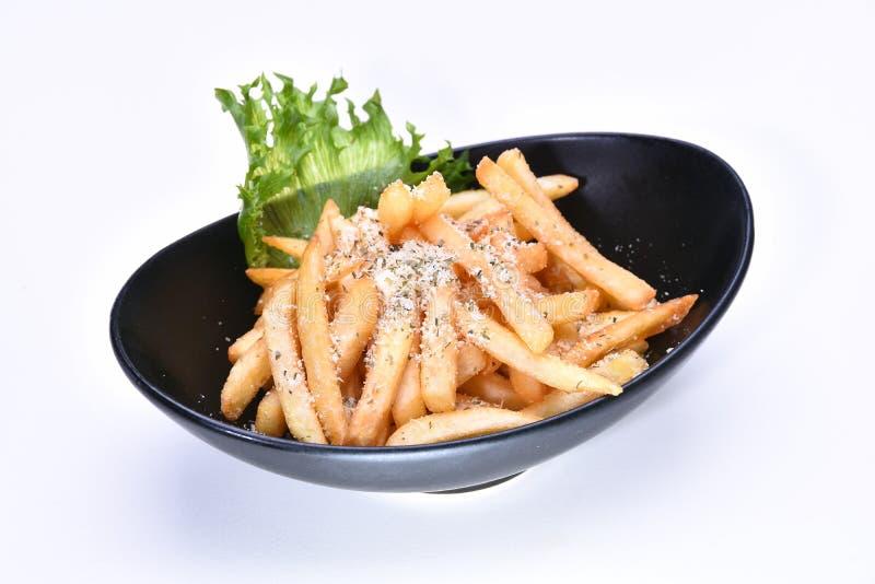 Eine Schüssel Pommes-Frites, die mit Parmesankäseparmesankäse-Weißhintergrund übersteigen lizenzfreies stockfoto
