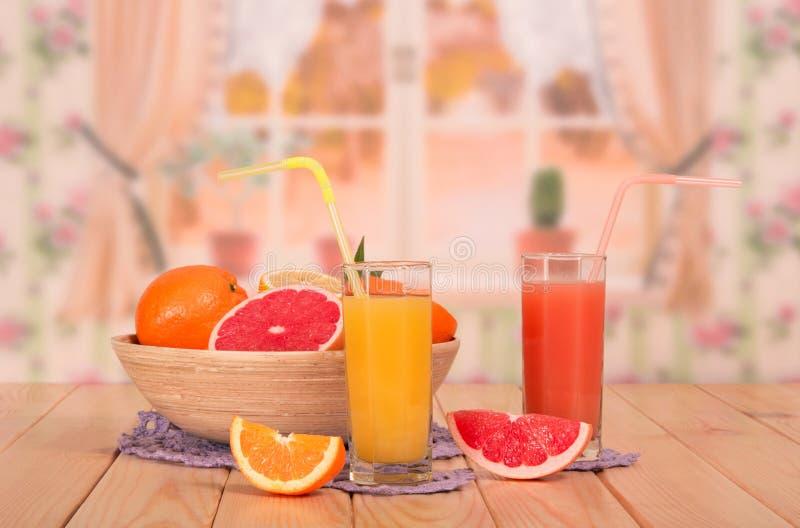 Eine Schüssel Zitrusfrucht, Gläser der Orange und Grapefruitsäfte lizenzfreies stockfoto