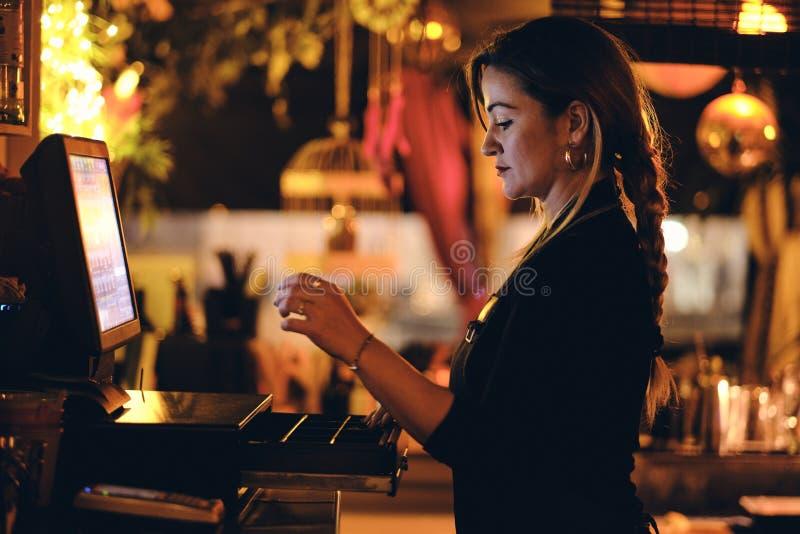 Eine sch?ne junge Frau am Schreibtisch in einem Restaurant stockbild