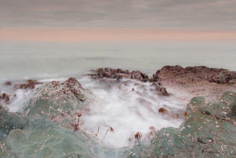 Eine sch?ne Landschaft der Welle spritzend bei dem Sonnenaufgang stockbild
