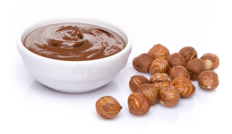Eine Schale der Schokoladenhaselnusses verbreitete mit Haselnüssen lizenzfreie stockfotos