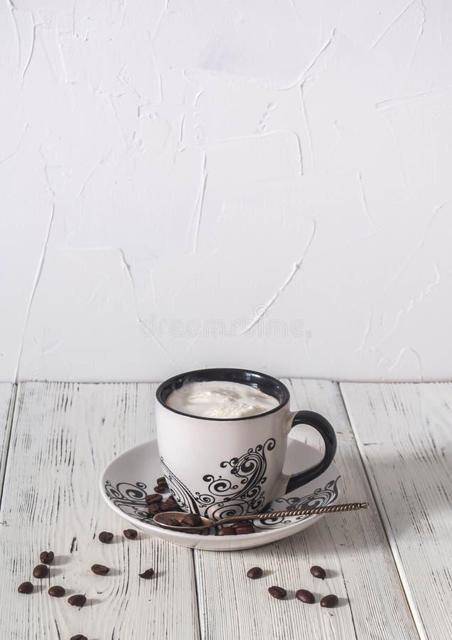 Eine Schale des Morgenkaffees mit Sahne, der Kaffeebohnen und des Löffels auf einem Holztisch lizenzfreie stockbilder