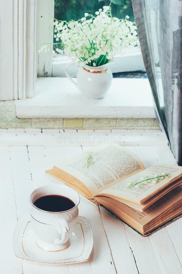 Eine Schale des schwarzen Kaffees und des offenen Buches auf einer Retro- Tabelle der weißen hölzernen Weinlese und des Blumenstr lizenzfreie stockfotografie