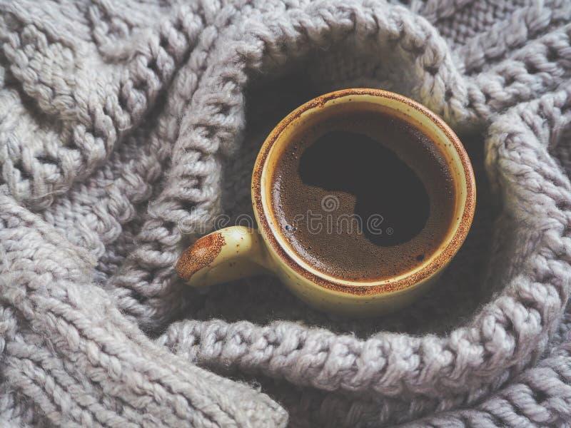 Eine Schale Espresso in einer Winterstrickjacke Das Konzept des häuslichen Komforts, der Gemütlichkeit und der Wärme stockfotografie