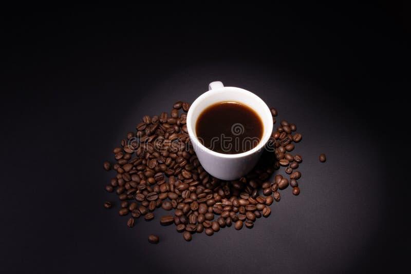 Eine Schale gebrauter Kaffee unter den Kaffeebohnen auf einer dunklen Oberfläche lizenzfreie stockfotos