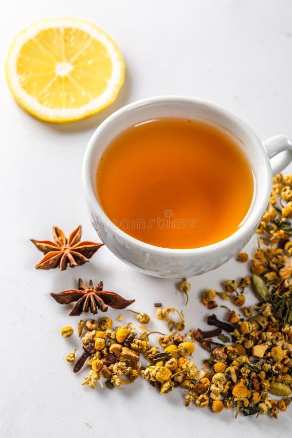 Eine Schale grüner Tee mit getrockneten Kamillenblumen und eine Scheibe der geschnittenen Zitrone auf einem weißen Hintergrund Di lizenzfreies stockfoto
