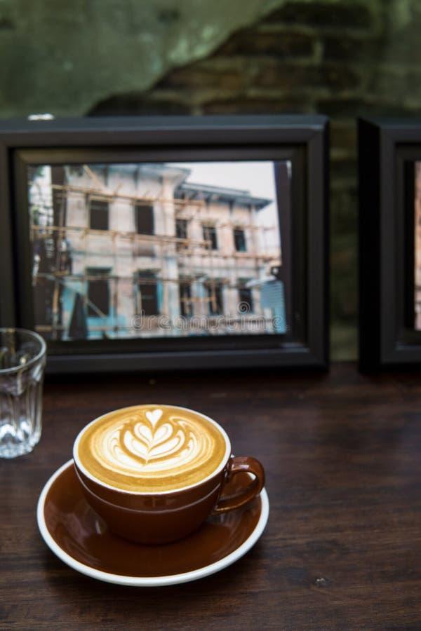 Eine Schale heißer Kaffee mit Flügeltulpenmuster auf hölzernem Zähler mit Bild- und Wasserglashintergrund stockbild