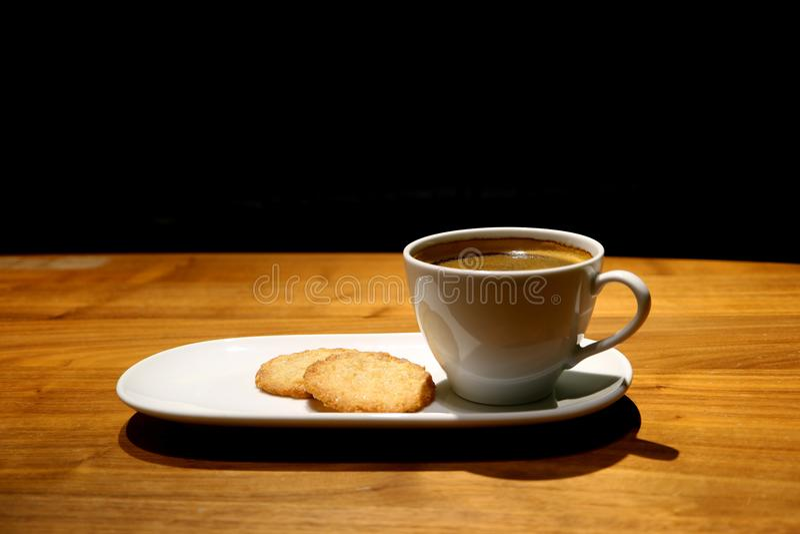 Eine Schale heißer Kaffee und Plätzchen diente auf Café ` s Holztisch auf schwarzem Hintergrund, mit freiem Raum für Text und Des lizenzfreies stockfoto