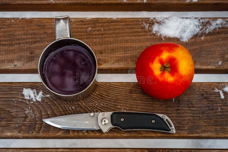 Eine Schale mit Tee und ein Messer in einer Holzbank im kalten Winter stockfotografie