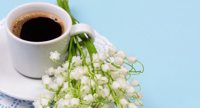 Eine Schale schwarzer Kaffee auf einer Untertasse und ein Blumenstrauß von Maiglöckchenblumen auf einem hellblauen Hintergrund lizenzfreies stockbild