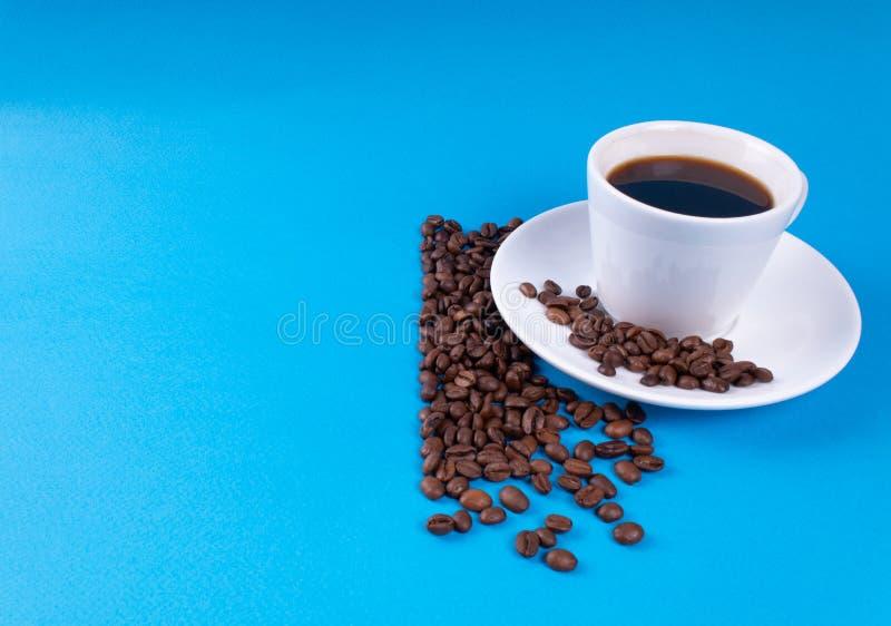 Eine Schale schwarzer Kaffee mit K?rnern nahe ihr auf einem blauen Hintergrund stockbild