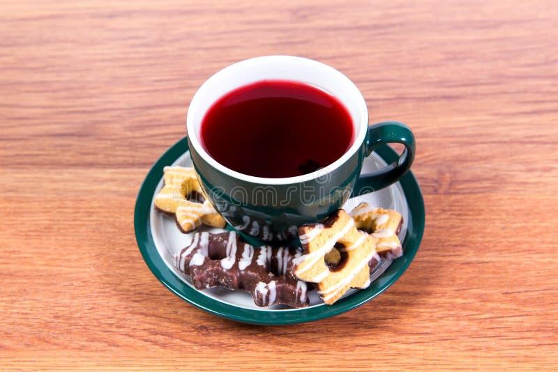 Eine Schale wohlriechender schwarzer Tee in einem Porzellanbecher und -Keks bedeckt mit Schokolade auf einer Platte - köstliches  lizenzfreies stockbild