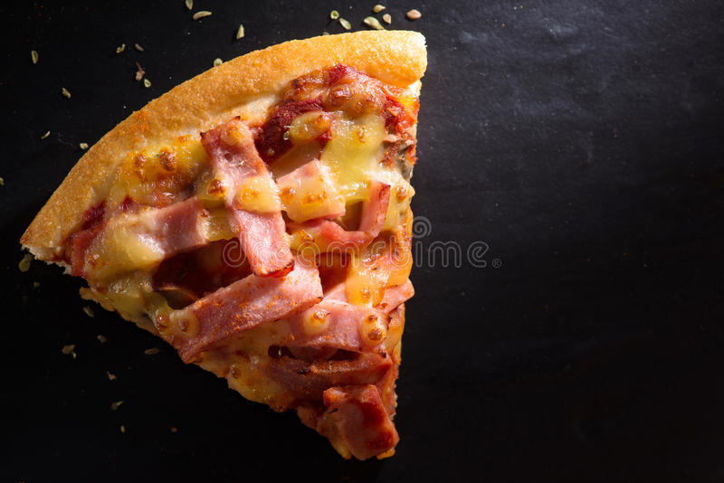 Eine Scheibe der Pizza ist auf einer Steinplatte stockfotos