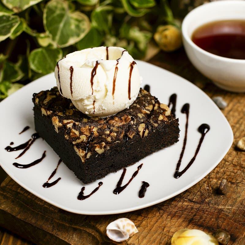 Eine Scheibe des Schokoladenschokoladenkuchens mit Walnuss und Vanilleeis stockfotografie