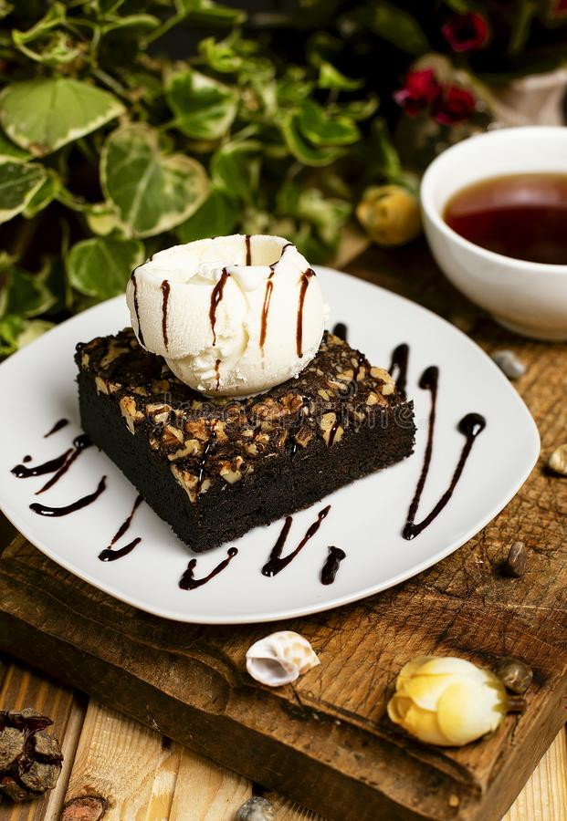 Eine Scheibe des Schokoladenschokoladenkuchens mit Walnuss und Vanilleeis stockbild
