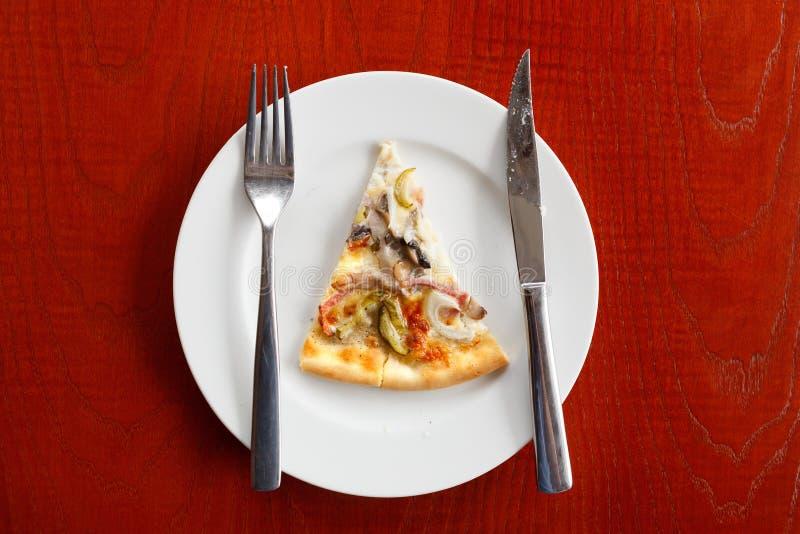 Eine Scheibe Pizza auf einer weißen Platte Holztischmesser und -gabel lizenzfreies stockfoto