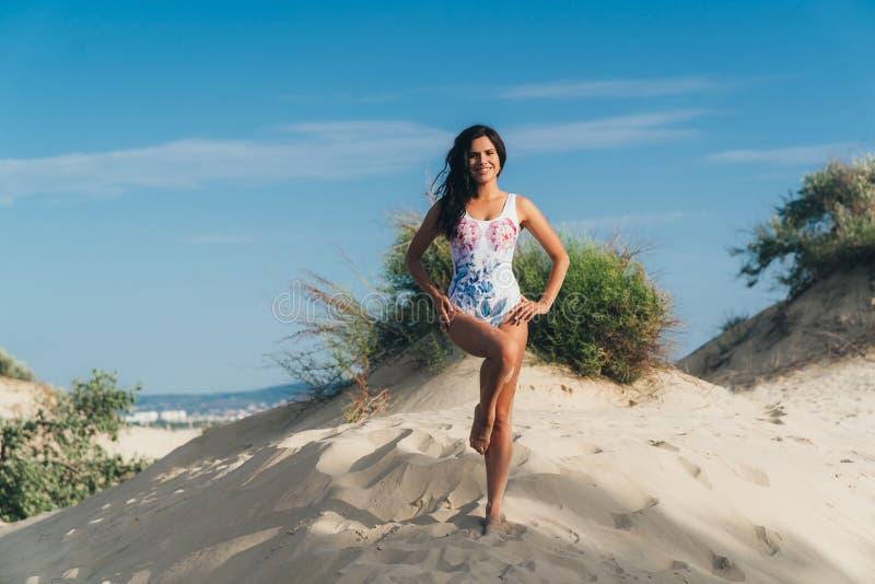 Eine schlanke schöne europäische Frau, die auf einem leeren Strand, einen Badeanzug tragend aufwirft und nett lachen und genießen lizenzfreies stockfoto